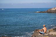 Man sitting on a rock looking to the sea - SIPF000421