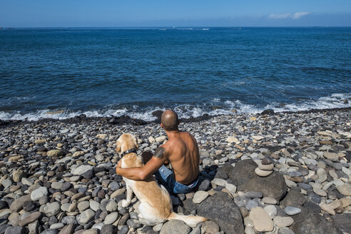 Back view of man sitting on stony beach with his dog looking at the sea - SIPF000424