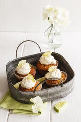 Four lime cup cakes with cream cheese topping on metal tray - EVGF002945