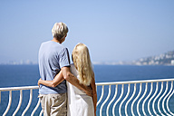 Senior couple looking at view on balcony by the sea - ABAF002007
