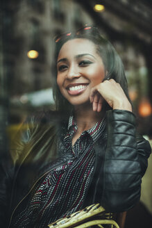 Portrait of smiling young woman sitting behind windowpane of a cafe - ZEDF000090