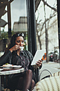 Portrait of young woman sitting in a cafe looking at digital tablet while drinking coffee - ZEDF000093