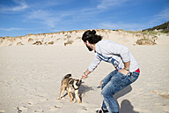 Man playing with his mongrel on the beach - RAEF001140