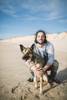 Man with his mongrel on the beach - RAEF001146