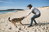 Man playing with his mongrel on the beach - RAEF001152