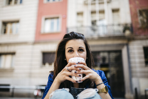 Spain, Barcelona, young woman with a coffee in the city - JRFF000613