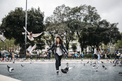 Spain, Barcelona, playful young woman with pigeons on a square - JRFF000619