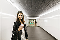 Portrait of smiling young woman in a tunnel - JRFF000625