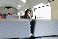 Young woman on train looking out of window - JRFF000631