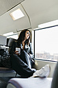 Young woman on train looking out of window - JRFF000634