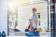 Smiling young woman holding shopping bags looking in shoe shop - DIGF000397