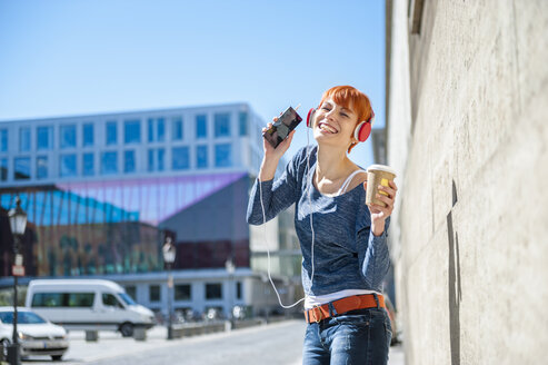 Happy young woman with coffee to go listening to music - DIGF000448