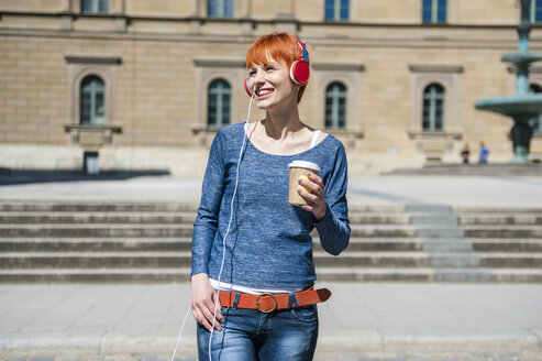 Smiling young woman with coffee to go listening to music - DIGF000451