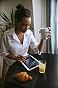 Young woman using digital tablet at breakfast table - ZEDF000100