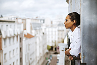France, Paris, young woman at attic leaning out of window - ZEDF000106