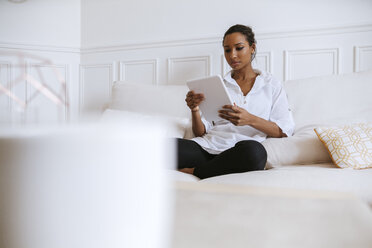Young woman sitting on couch using digital tablet - ZEDF000109