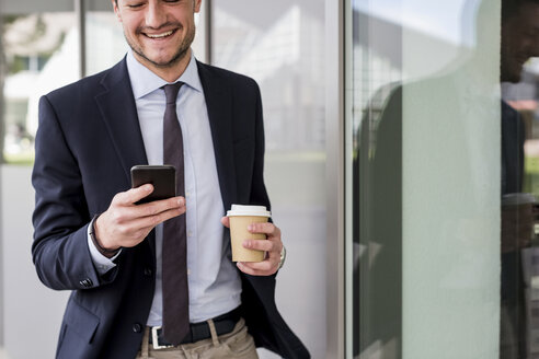 Smiling businessman looking at cell phone outdoors - MAUF000509