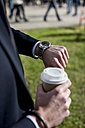 Businessman outdoors with coffee to go checking the time - MAUF000515