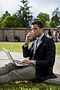 Businessman sitting on meadow with laptop and coffee to go - MAUF000524