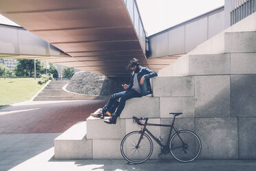 Spain, Bilbao, Man with smartphone and headphone, racing cycle - RTBF000184