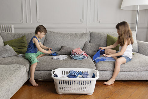 Siblings folding laundry together on the couch - LITF000275