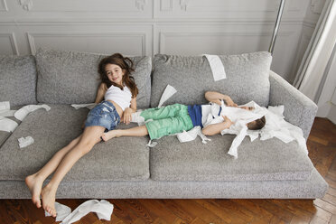 Siblings laying on the couch surrounded by mess of toilet paper pieces - LITF000278