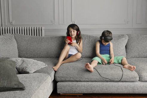 Siblings sitting on the couch listening  music with their headphones and smartphones - LITF000281