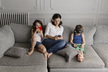 Mother and her children sitting on the couch listening music with their headphones and smartphones - LITF000284