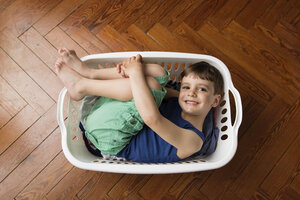 Portrait of smiling little boy curled up in laundry basket - LITF000287