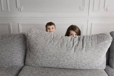 Two little children hiding behind the couch - LITF000290