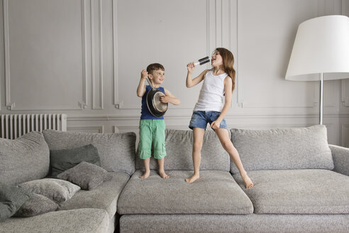 Two little children playing with pan and brush on the couch - LITF000293