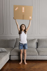 Portrait of little girl holding a cardboard box over her head at home - LITF000296