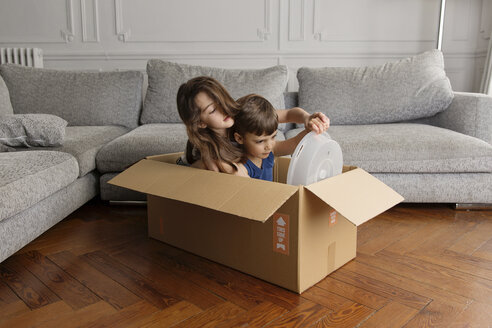 Girl and little brother playing together in a cardboard box at home - LITF000299
