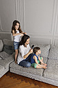 Mother and her children in a row together on the couch combing their hair with hairbrushes - LITF000302