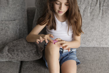 Little girl putting a band-aid on her knee - LITF000305