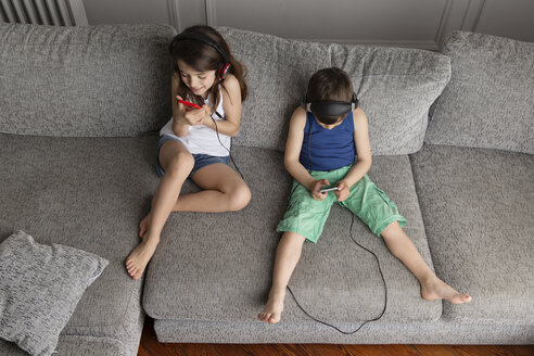 Siblings sitting on the couch listening  music with their headphones and smartphones - LITF000308