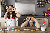 Little girl and boy covering their eyes with cookies - LITF000311