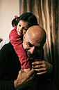 Happy grandfather playing with his granddaughter at home - JASF000720