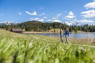 Germany, Bavaria, couple walking at lake Barmsee - DIGF000478
