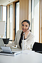 Smiling businesswoman at office desk on the phone - CHAF001689