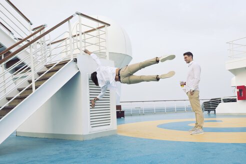 Two young men messing about on cruise ship, doing gymnastics - SEF000904