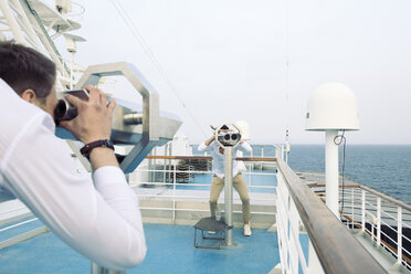Two young men on a ship watching each other through telescopes - SEF000907