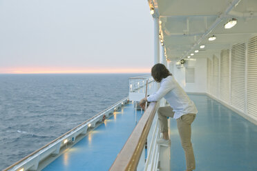 Young man standing on deck of ship, watching sunset - SEF000910