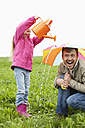 Father with watering can and daughter with umbrella on meadow - MAEF011613