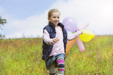 Young girl running with balloons over meadow - MAEF011616