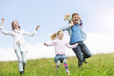 Carefree family running in meadow - MAEF011618