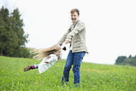 Happy father turning daughter in meadow - MAEF011624