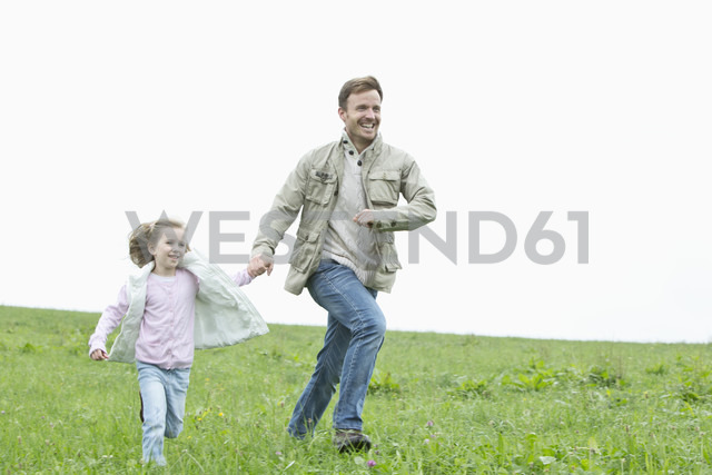 Happy father and daughter running in meadow - MAEF011627