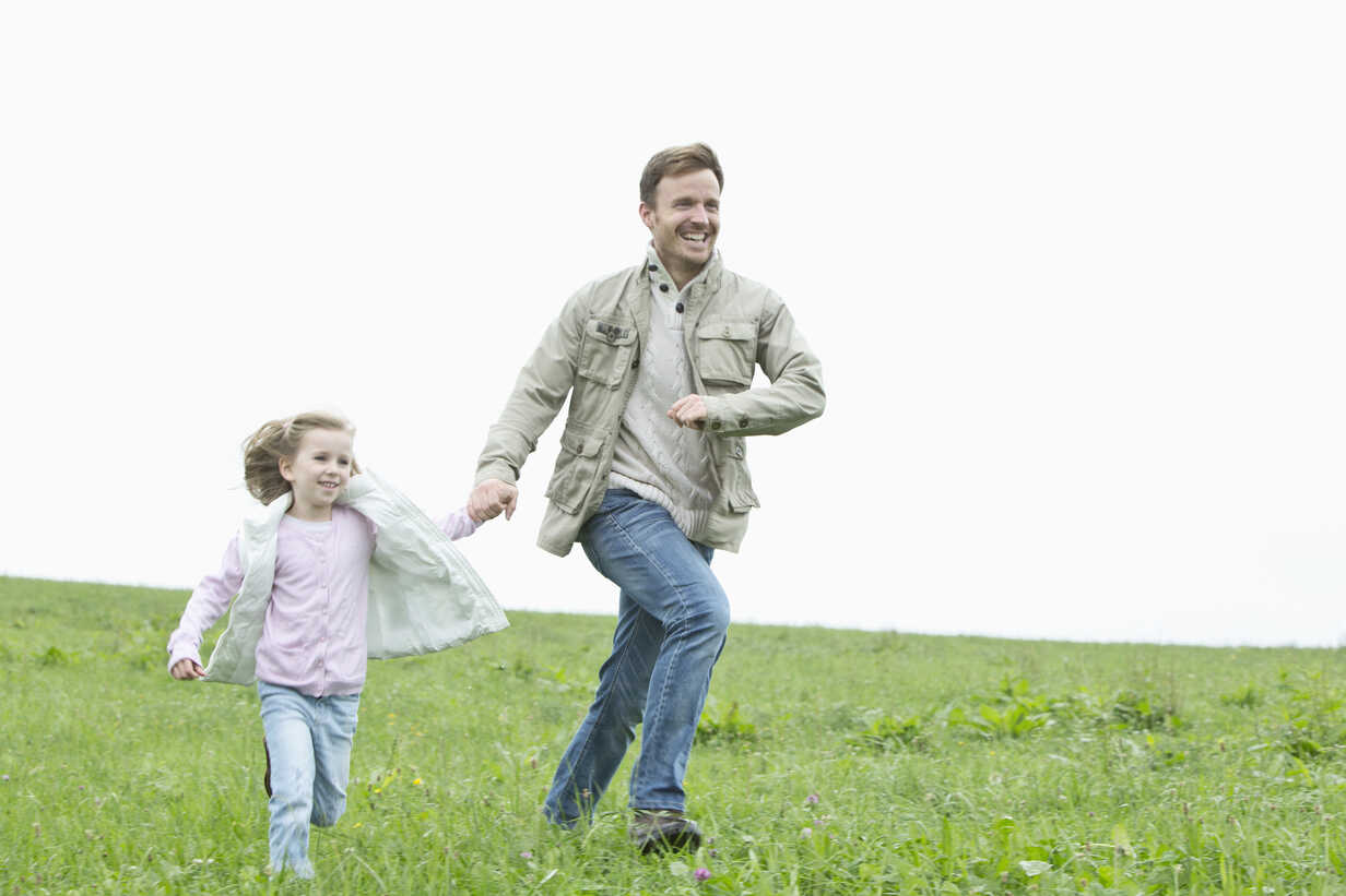 Happy father and daughter running in meadow - MAEF011627 - Roman Märzinger/Westend61