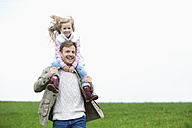 Happy father carrying daughter on shoulders on meadow - MAEF011630
